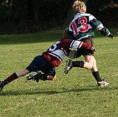 Dziecko uciekające przed kamerą w zielono-czarnej koszulce do rugby z obręczami jest atakowane wokół bioder i nóg przez inne dziecko w stroju przeciwnika.