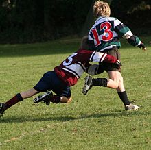 A child running away from camera in green and black hooped rugby jersey is in the process of being tackled around the hips and legs by an opponent.