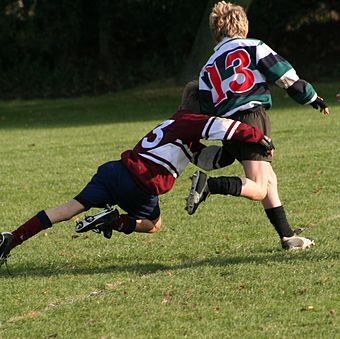 A rugby tackle must be below the neck with the aim of impeding or grounding the player with the ball. Schoolkids doing a rugby tackle.jpg
