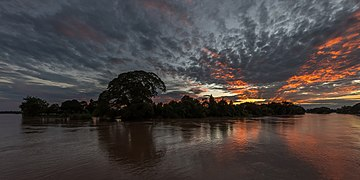 Silhouette of an island at dusk with red and grey clouds in Don Det Si Phan Don Laos.jpg