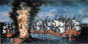 A colorful oil painting showing a large group of sailing warships engaged in battle. In the foreground to the left, a very large ship flying a Swedish flag is listing heavily and a huge explosion is shattering her structure and throwing men and equipment upwards in together with flames and black smoke