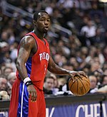 "A basketball player wearing a black jersey with the word ""PISTONS"" and the number 3 on the front"