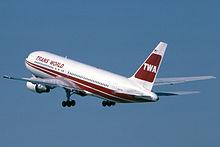 Jato da TWA com libré vermelha e branca durante a decolagem, com trens de pouso ainda abaixados.
