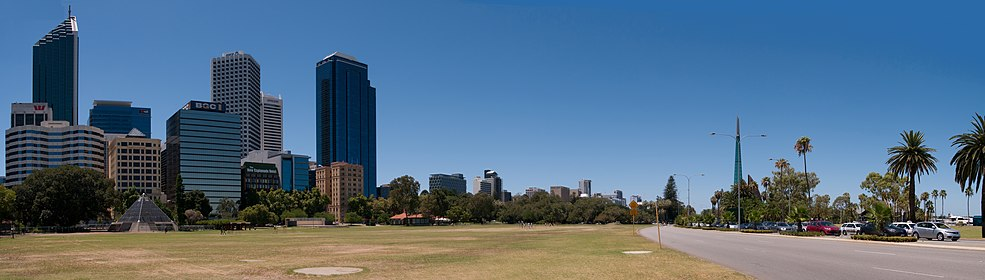 Tall buildings of Perth CBD on the left, grass parkland in the centre, road and foreshore to the right, with bell tower in background