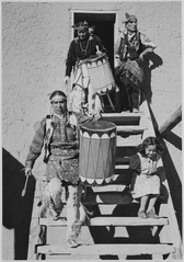 "Two Indians descending wooden stairs, carrying drums, another Indian and child near by, ""Dance, San Ildefonso Pueblo, Ne - NARA - 519978.tif"