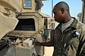 US Army 51270 CAMP LIBERTY, Iraq - Spc. Edric Ashley, a light-wheel vehicle mechanic, from Houston, indicates where the motor to the windshield washer fluid is found under the hood of a humvee, here, Sept. 22. It.jpg
