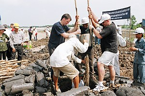 US Navy 031120-C-0000T-001 Sailors assigned to USS Vandegrift (FFG 48) assist local workers in digging a foundation for a new school building at Doi Lau Hamlet Kindergarten.jpg
