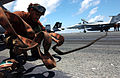 US Navy 040530-N-8148A-030 Aviation Electronics Technician 3rd Class Ariana Gomeztorres, of New York City, N.Y., stretches out a fire hose prior to washing down an F-A-18F Super Hornet.jpg