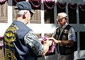 US Navy 041112-N-5539C-002 Mr. Al Shoehigh, right, receives a lei to place on a plaque of commemorating the submarines who were lost during World War II, at the Naval Submarine Memorial during a Veterans' Day Service on N.jpg