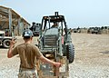 US Navy 070515-N-3560G-051 Equipment Operator 3rd Class Mathew Roy of Naval Mobile Construction Battalion (NMCB) 4 directs Equipment Operator 1st Class Joie McCarty during forklift operations.jpg