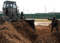 US Navy 070605-N-7367K-006 Equipment Operator 1st Class Edwin Ortiz, assigned to Naval Mobile Construction Battalion (NMCB) 1 Seabee, guides a front-end loader to fill a hole in a simulated runway.jpg