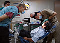 US Navy 080716-N-6387D-002 Sammy M. Baho, a University of California San Diego, Pre-Dental Society senior undergraduate student, looks on as South Korean navy Lt. Michael Sim performs a dental procedure.jpg