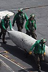 US Navy 090706-N-9132C-280 Aviation Machinist's Mates assigned to the Fist of the Fleet of Strike Fighter Squadron (VFA) 25, move a drop tank across the flight deck of the aircraft carrier USS Ronald Reagan (CVN 76).jpg