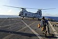 US Navy 100908-N-8335D-371 Ship's Serviceman Seaman Joseph Davis runs for safety after removing a chock and chain from a CH-46 Sea Knight helicopte.jpg