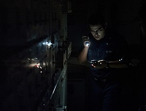 US Navy 120110-N-DR144-402 Electrician's Mate 3rd Class Juan Murillo eports the status of an electrical load center during a loss of power drill.jpg
