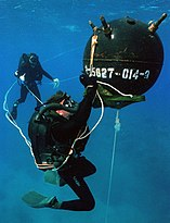 A diver appears to work on a large spherical mine, with another diver observing from a distance in the background