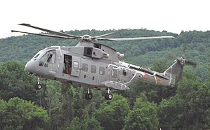 Five-bladed gray helicopter landing in the middle of bush land