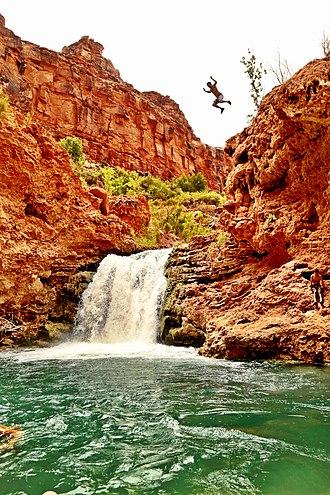 Jumping platform - Man jumping off cliff in Arizona.