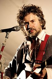 Bearded, curly haired man playing a guitar onstage