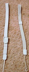 A picture of two light-grey wrist straps laid parallel and vertically on beige carpet