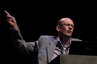 Photo shows a close up of Jon Davies speaking on a stage