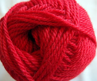 Worsted yarn spun with average to hard twist from long combed and carded fibers, traditionally of wool