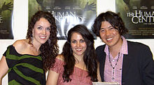The heads and upper bodies of three people side by side, posing for the camera smiling. At the left, and centre are two white women in their mid-twenties, both with long dark-brown hair. The woman on the left is wearing black and green clothing, and the woman in the centre is wearing pink. At the right is a Japanese man in his early-thirties, with dark centre-parted hair. He is wearing a pink open-collar shirt, and a black suit-jacket.