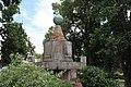 15.Ondřejov pomník padlým detail vrcholu pomníku s nápisem PADLI ABY OŽILA VLAST letopočtem MCMXXVIII šikmý pohled z úrovně trávníku pře keře.JPG