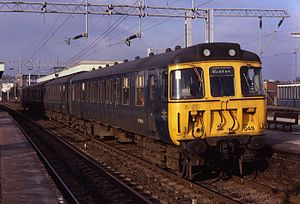 British Rail Class 310 - Class 310 train in British Railways plain blue at Watford Junction station. The driving cab features wrap-around windows as originally fitted to these trains.
