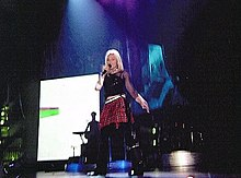 Madonna wearing a skirt dancing on a blue it stage, in front of a video screen.