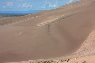 "Great Sand Dunes National Park and Preserve - Hiker ascending the 700' tall ""High Dune"""