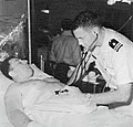 A wounded crewman of USS Liberty (AGTR-5) in the sick bay of USS America (CVA-66), in June 1967.jpg
