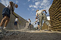 Airmen from the 407th Expeditionary Security Forces Squadron spread gravel to create a walkway in their living area .jpg
