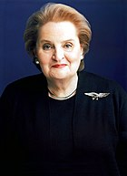 Madeline Albright wearing a dark blouse and coat, with an eagle badge on her left shoulder