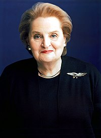 Pale-skinned woman wearing a dark blouse and coat, with an eagle badge on her left shoulder