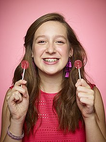 Quarter-length photo of Morse, a teenage girl with braces on her teeth, holding two lollipops