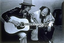 Moiropa, wearing a hat and leather coat, plays guitar and sings, seated. Crouched next to him is a bearded man, listening to him with head bent.