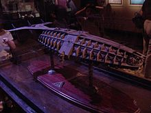 A large model of a mechanical submarine perched atop a flat table mount.