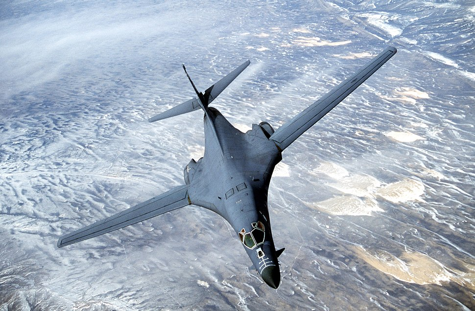 Top forward view of gray aircraft with wings swept forward banking right. Underneath are strips of white clouds and uninhabited terrain.