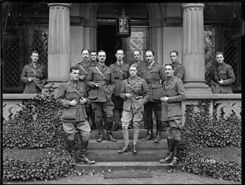 Several men dressed as military officers standing on the verandah of a stone building