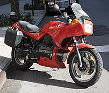 Red BMW K75S with topbox and panniers, parked on a city street.