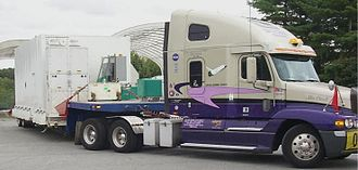 Semi-trailer truck - Semi-trailer tractor with sleeper behind the cab and oversize load on lowboy trailer