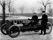 Henry Ford, standing, and Barney Oldfield in 1...
