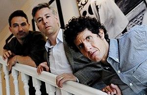 Um grupo de três homens em uma escada atrás de um fundo claro