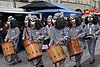 A group of drummers wearing costumes to look like dogs wearing prison dress, playing as they walk along a narrow street