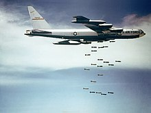 Against a blue sky with white clouds, a B-52F releases bombs over Vietnam.