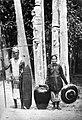 COLLECTIE TROPENMUSEUM Een koppensneller met aan zijn gordel een schedel die bij feesten gebruikt wordt om uit te drinken een vrouw met een grote 'blangai' pot en achter hen palen voor het dodenfeest 'Tiwah' Borneo TMnr 10002945.jpg