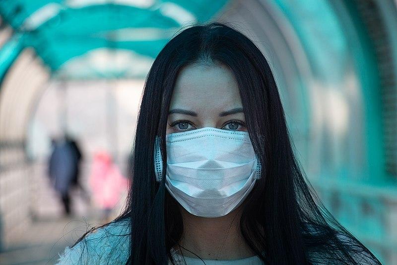 Femme portant un masque médical dans la rue pendant l'épidémie du coronavirus | Photo : Wikimedia Commons.