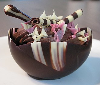 Edible tableware - A chocolate mousse cupcake with edible chocolate straws (top-center) and an edible chocolate spoon (upper left)