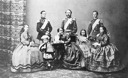 Christian IX of Denmark with his wife and their six children, 1862. Left to right: Dagmar, Frederick, Valdemar, Christian IX, Queen Louise, Thyra, George and Alexandra Christian IX of Denmark and family 1862.jpg